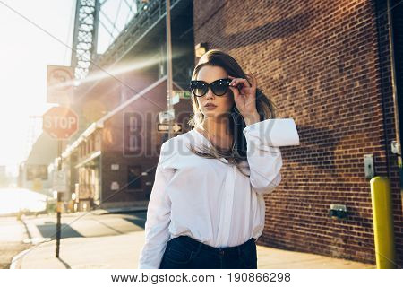 Elegant business woman wearing glasses and white t-shirt at hot summer day in the city