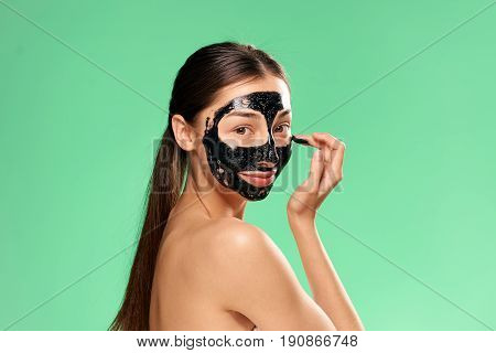 woman in cosmetic mask on a green background.