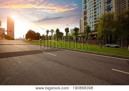 Empty City road surface floor with streetscape buildings of golden yellow sunset