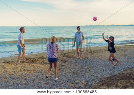 A group of young and cheerful friends playing volleyball on a wild beach during sunset. The girl hit a volleyball