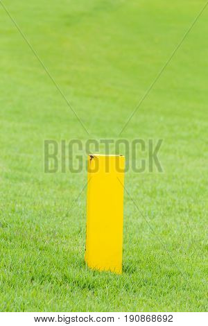 The yellow distance marker pole to inform range of golfing in green golf course.