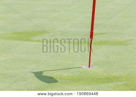 Close up golf hole with flagpole on green grass and its shadow in green golf course.