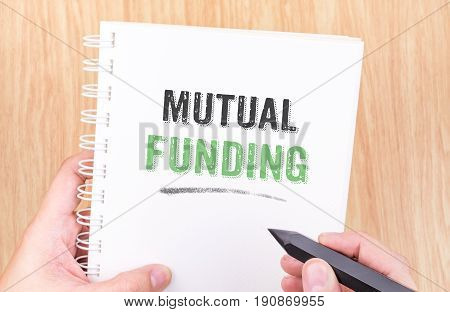 Mutual Funding Word On White Ring Binder Notebook With Hand Holding Pencil On Wood Table,business Co