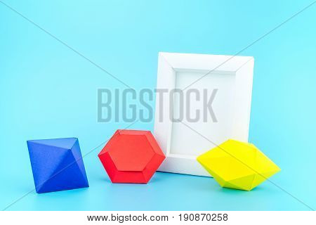 White Photo Frame(made From Paper) And Colourful Paper Jewels On Light Blue Background,modern Home D