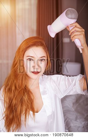 Woman Using Hair Dryer In Bedroom With Soft Light
