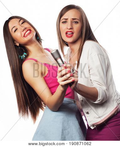 lifestyle and people concept: Happy girls friends with microphone over white background