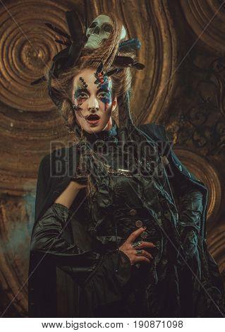 Young  woman wearing dark costume. Bright make up and smoke-  halloween theme.