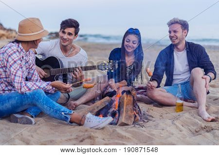 group of young and cheerful friends sitting on beach and lit bonfire. One man is playing guitar. Music on Wild beach. They fry sausages