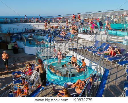 Miami, United States of America - January 12, 2014: The people resting at Carnival Glory Cruise Ship, the ship leaving Miami, USA on January 12, 2014. Carnival Glory is a Conquest-class cruise ship built in 2003 with capacity of 2974 passengers
