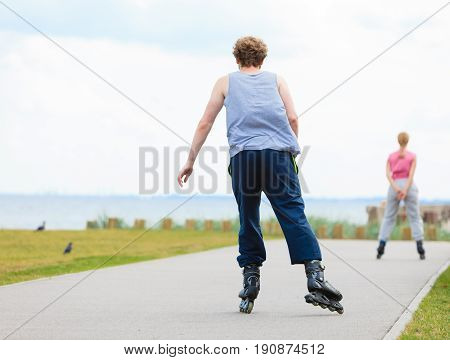 Man Rollerblading Behind Woman On Promenade
