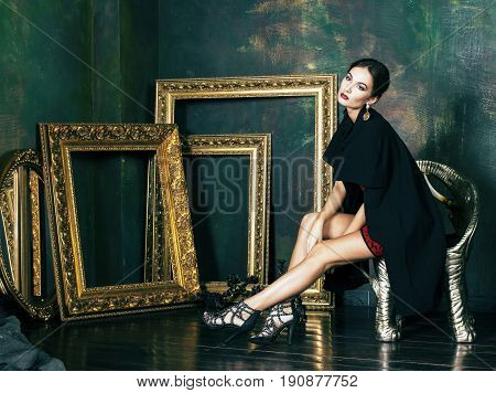 beauty rich brunette woman in luxury interior near empty frames, wearing fashion clothes, lifestyle pretty real people concept close up