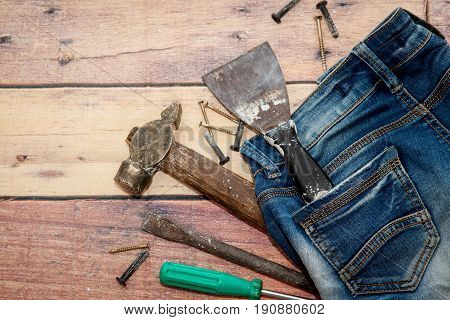 A hammer, a screwdriver and nails are lying on old jeans on a wooden background. Repair and construction
