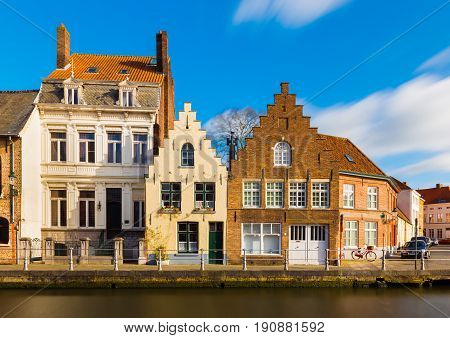 Bruges (Brugge) Belgium: Street view of the old residential houses in traditional architecture style. Facades of the historical buildings and canal with water.
