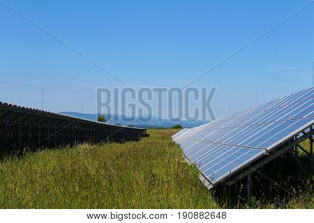 Photovoltaic solar panels with grass in czech landscape.