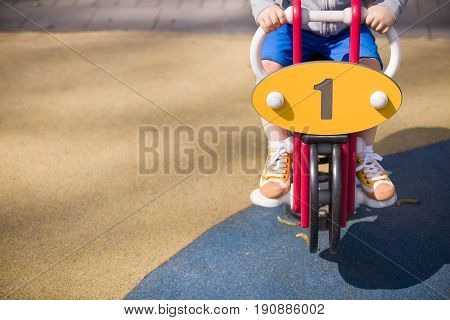 Toddler boy sitting on swing car and keeping balance. Child playing on outdoor playground on a sunny summer day.