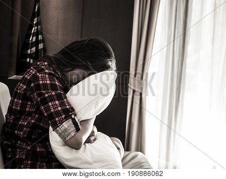 sad woman hug white pillow and cry. Sad woman sitting alone in a empty room beside window or door