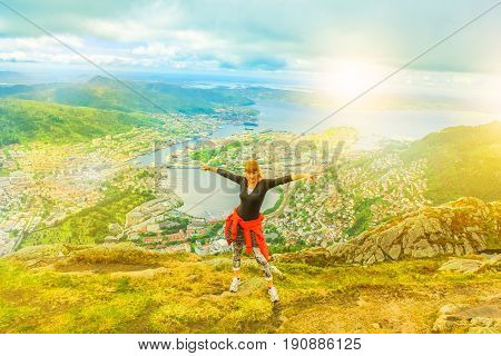 Happy traveler enjoying after hiking on Mount Ulriken at sunset. Norwegian tourism highlight. Bergen city skyline. Kiker woman in North Europe. Scenic norwegian landscape. Popular overlook landmark.