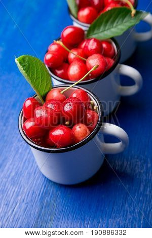 Cherry In Enamel Cup On Blue Wooden Background. Healthy, Summer Fruit. Cherries...