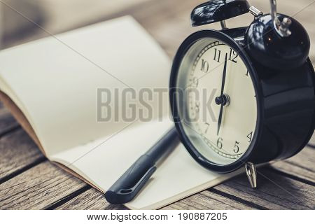 retro clock time at 6 o'clock with notebook or memo on wood table times of memory writing diary concept vintage color tone.