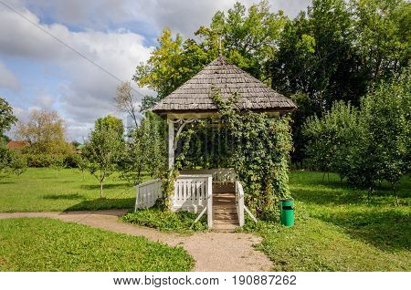 Small white wooden gazebo in park of Petrovskoe village. State Museum-reserve of A. S. Pushkin Pskov Region Russia.