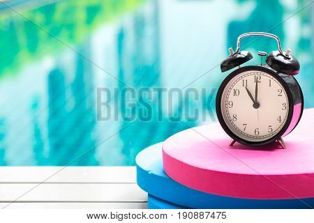 Swimming Times, Retro Black Bell Clock Time At 11 O'clock At Swimming Pool Blur Background.