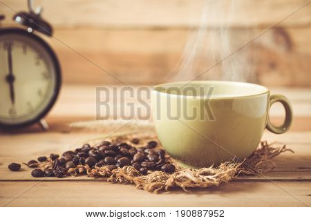 Morning Aroma Hot Black Coffee Or Americano And Arabica Coffee Bean With Smoke On Wood And Clock Bac