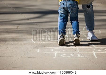 Closeup of woman's and toddler's legs on drawn hopscotch on the pavement. Activities with children outdoors.