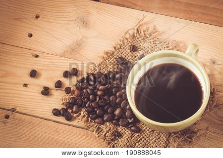 Aroma Hot Black Coffee Or Americano And Arabica Coffee Bean With Smoke On Wood Background.