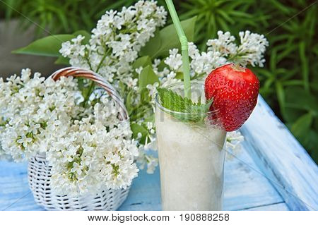 Milk smoothie with banana and strawberries on a background of flowers white lilac. A horizontal frame.