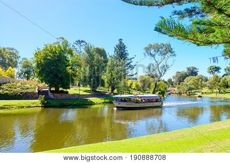 Adelaide Australia - April 14 2017: Iconic Pop-Eye boat with people on board traveling downstream in Torrens river near Adelaide CBD on a bright day