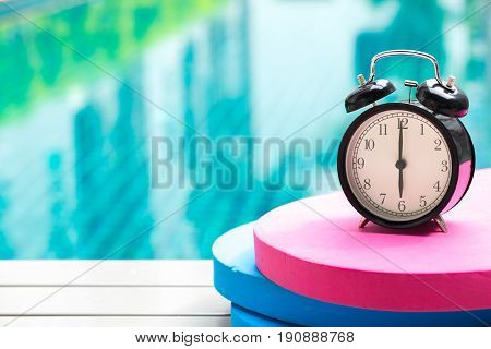 Swimming Times, Retro Black Bell Clock Time At 6 O'clock At Swimming Pool Blur Background.