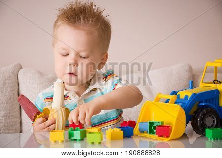 Portrait of cute toddler boy eating ice-cream and banana and playing with toy tractor with colorful plastic bricks or details on it. Activities at preschool or nursery. Childhood and education concept