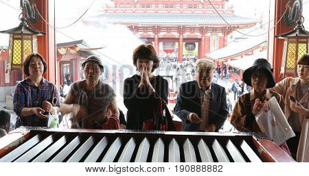 Tokyo, Japan - April 19, 2017: people offering and praying at Hozomon Gate of Buddhist Temple Senso-ji, Asakusa, the oldest temple in Tokyo from main hall of Kannon Temple.