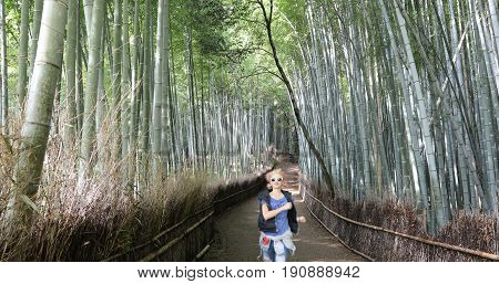 Happy tourist woman running in bamboo forest at Sagano in Arashiyama, Kyoto, Japan. Travel asia concept. Freedom and enjoying concept. Kyoto's popular landmark and touristic destination.