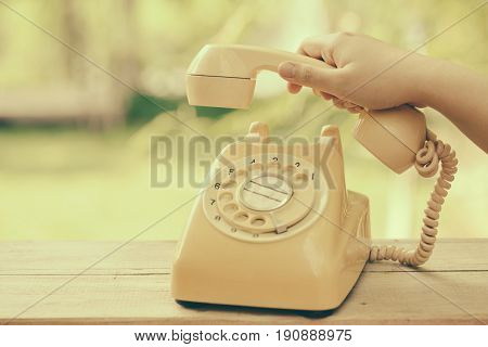 reception receive the phone call in retro style dial telephone vintage color tone.