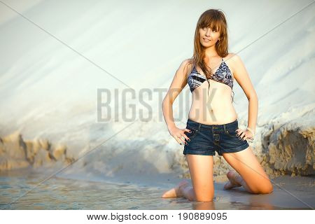 Young beautiful girl is kneeling on the beach on a sand mountain background. She is dressed in denim shorts and a bra. Warm sunset light
