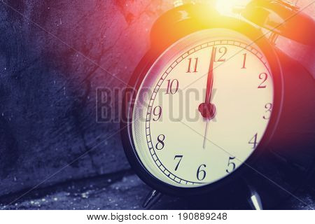 12 O'clock Vintage Clock At Dark Color Tone With Sun Light Memory Time Concept.