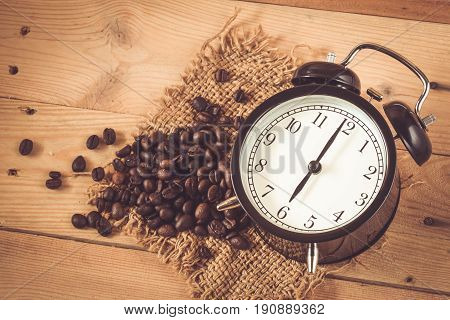 6 O'clock Retro Clock With Arabica Coffee Bean On Sack And Wood Background Table.