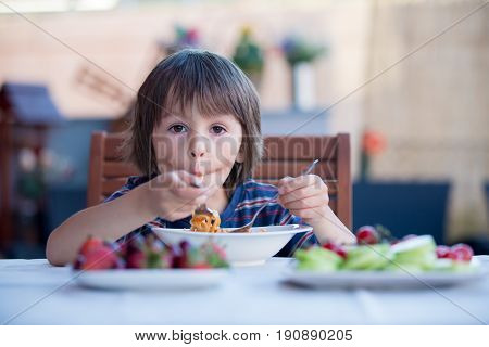Cute Child, Preschool Boy, Eating Spaghetti For Lunch Outdoors In Garden