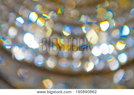 Chandelier and glare blurred focus. The colors are yellow blue red green orange. Soft focus