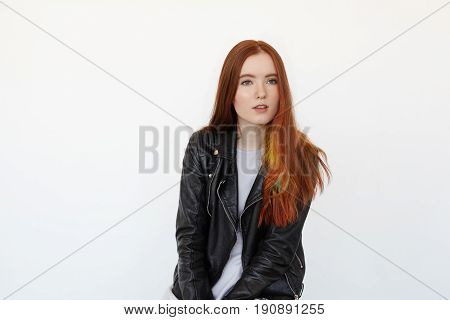 Portrait of the beautiful female model with long red hair and green eyes in black leather jacket attentively listening to the interlocutor. Hipster student female resting after lecture in college