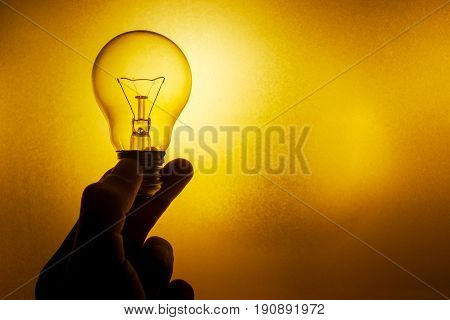 Golden Light Bulb, Silhouette Hand Hold Clear Glass Tungsten Lighting Bulb Or Twisted Candle Bulb On