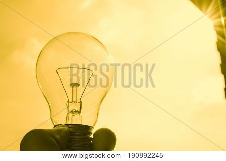 Golden Light Bulb, Hand Hold Clear Glass Tungsten Lighting Bulb With Sky And Sun Gold Color Backgrou