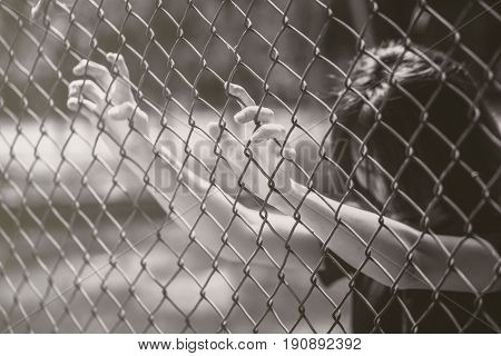 Teen Behide The Cage Or Woman Jailed, Unhappy Girl Hand Sad Hopeless At Fence Prison In Jail, No Fre