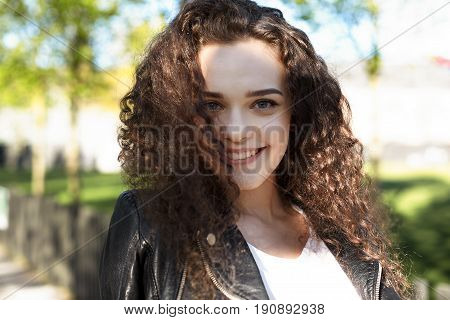 Portrait of gorgeous Caucasian curly young woman looking at camera with cheerful smile. Happy student female wearing leather jacket relaxing outdoors after college. People youth and lifestyle concept