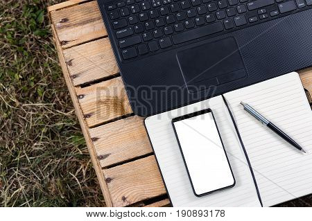 Notepad with laptop and bezel less smartphone with blank screen. Freelance work outside of the office.