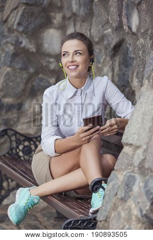Youth Lifestyle Concepts. Pretty Smiling Caucasian Brunette Woman Relaxing on Bench and Listening to Music on Smartphone. Vertical Image