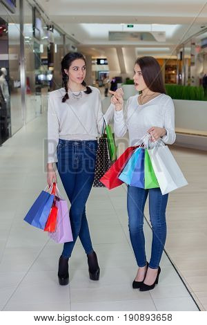 Two Cute Girl Walks In Mall With Gift Bags.