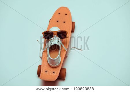 High angle view of hipster penny board one sneaker and sunglasses making smiley composition