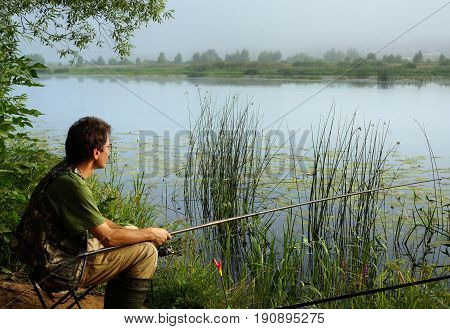 Fisherman on a coast of river landscape in fog